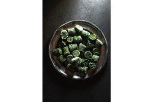 Frozen spinach in briquettes on a tin plate in the center of the table