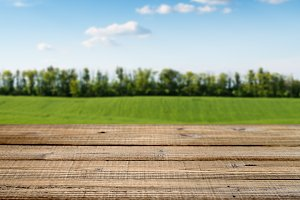 Old wooden table and green field