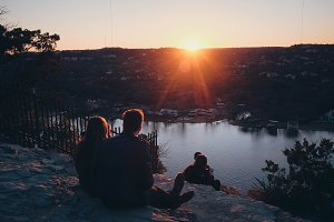Couple watching sunset from a hill
