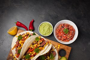 Three Mexican tacos with marbled beef, black Angus and vegetables on wooden Board on a dark stone background. Mexican dish with sauces guacamole and salsa in bowls. Top view with copy space