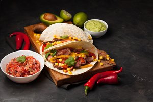 Three Mexican tacos with marbled beef, black Angus and vegetables on wooden Board on a dark stone background. Mexican dish with sauces guacamole and salsa in bowls. Top view