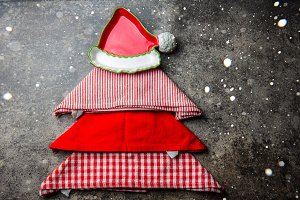 Christmas xmas food background with copy space. Christmas tree made from kitchen napkins and red plate. Gray stone ackground. Holiday menu or cooking concept