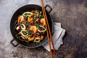 Buckwheat stir-fry noodles with seafood - shrimps, octopus, squid in cast iron asian wok with cooking chopstick. Top view, stone background