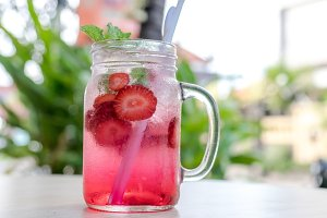 Refreshing iced strawberry lemonade in mason jar on a green nature background. Summer fresh concept.