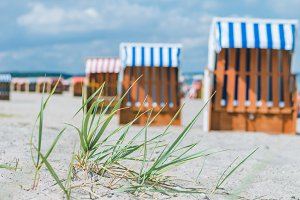 Blurred colourful beach roofed chairs on sandy beach in Travemunde, Germany