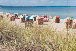 Colorful roofed chairs on sandy beach in Travemunde. Some grass in foreground. Germany
