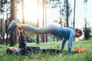 Two female friends doing partner plank exercise practicing pilates in the spring forest