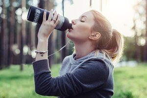 Portrait of fit young sportswoman with fair hair drinking water after morning exercises in the park