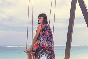 Beautiful young female sitting on the swing on sea shore. Bali island, Indonesia. Pandawa beach.