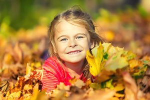 Happy little girl plays with autumn leaves