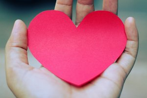 Red paper heart shape in hand