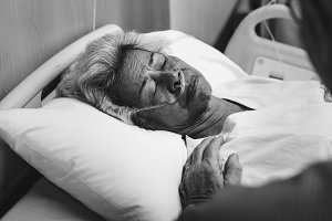 Old patient in a hospital bed