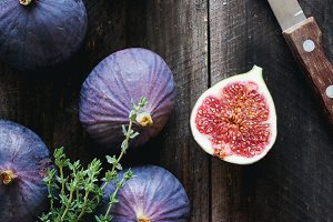 Purple figs, red apple and fresh thyme on wooden table