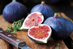 Purple figs sliced on wooden board