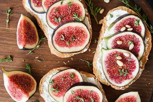 Appetizer bruschetta or toast with fresh cheese, figs and honey