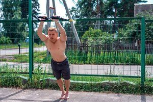 A male athlete is engaged in open air loop, trains triceps at fence. In summer, in shorts and a bare torso. Healthy lifestyle of young people.