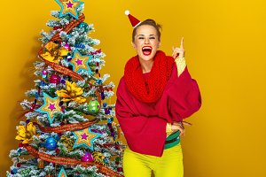 woman near Christmas tree on yellow background having idea