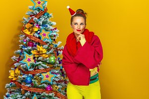 woman near Christmas tree isolated on yellow background