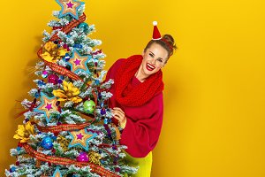 woman looking out from Christmas tree on yellow background