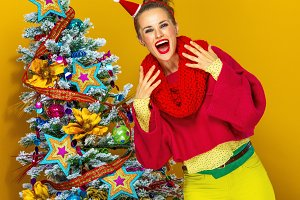 excited woman near Christmas tree isolated on yellow background