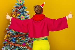 stylish woman near Christmas tree showing thumbs up