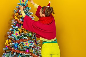 woman near Christmas tree on yellow background decorating