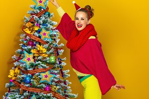 happy woman near Christmas tree on yellow background decorating