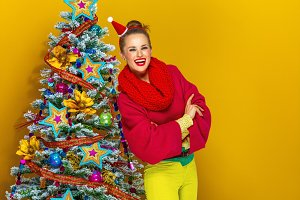 happy stylish woman near Christmas tree on yellow background