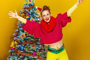 happy woman near Christmas tree on yellow background rejoicing