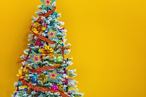 colorful Christmas tree isolated on yellow background