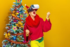 smiling woman near Christmas tree with VR glasses rejoicing