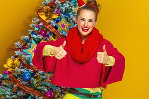 happy woman near Christmas tree showing thumbs up