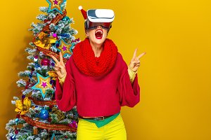 woman near Christmas tree with VR glasses showing victory