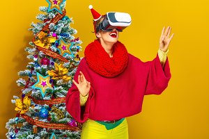 woman near Christmas tree wearing virtual reality glasses