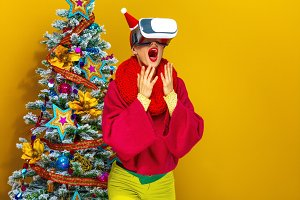 surprised woman near Christmas tree wearing VR glasses