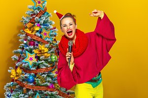 smiling woman with microphone singing near Christmas tree
