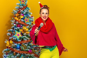 happy modern woman near Christmas tree giving microphone