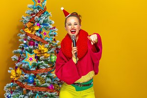 woman near Christmas tree with microphone pointing at camera
