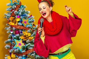 woman near Christmas tree with microphone singing