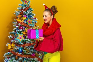 woman near Christmas tree looking at Christmas present box