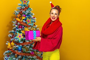 smiling woman with Christmas present box near Christmas tree