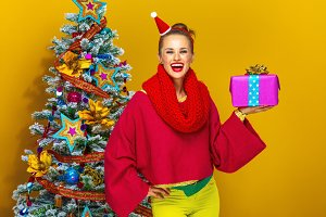 smiling stylish woman showing Christmas present box