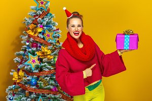 happy trendy woman pointing at Christmas present box
