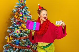 woman with Christmas present box taking selfie with mobile