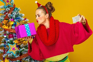 woman with Christmas present box taking selfie with mobile phone