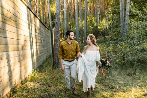 Newlyweds are walking in the forest. Girl in white dress and man in an olive shirt. Rustic wedding. Artwork.