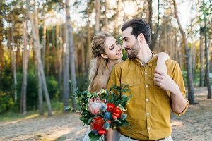 Beautiful bride embraces her groom by the shoulder. Wedding walk in a forest. A newlywed looks at each other. Girl in white dress and man in an olive shirt. Artwork.