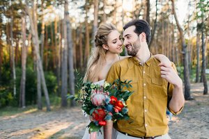 Beautiful bride embraces her groom by the shoulder. Wedding walk in a forest. Girl in white dress and man in an olive shirt. Artwork.