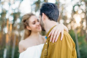 Bride is embracing groom's back by her tender hand. Blurred newlyweds look at each other with tenderness and love. Close-up. Artwork