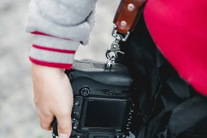 Photo camera on a leather strap. Photographer holds a camera in the hand. Close-up. A